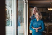 Lächelndes Seniorenpaar umarmt sich zu Hause — Stockfoto