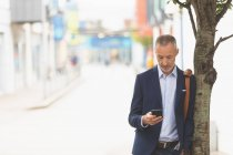 Businessman using mobile phone in city on a sunny day — Stock Photo