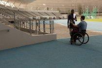 Два спортсмена-инвалида обсуждают по мобильному телефону в спортивном зале — стоковое фото