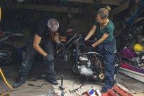 Male and female mechanicians repairing motorbike in repair garage — Stock Photo