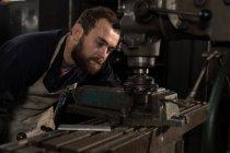 Aufmerksame Schmiede mit Pressbohrer in Werkstatt — Stockfoto