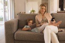 Мати і дочка, використовуючи цифровий планшет і мобільний телефон у вітальні на дому — стокове фото