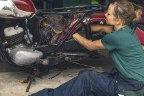 Primo piano di donna meccanico che ripara moto nel garage — Foto stock