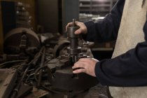 Mid section of blacksmith working in workshop — Stock Photo