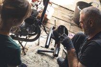Meccanici di sesso maschile e femminile che riparano moto in officina — Foto stock