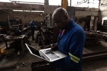 Side view of blacksmith using laptop in workshop — Stock Photo