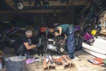 Mechaniker und Mechanikerinnen reparieren Motorrad in Werkstatt — Stockfoto
