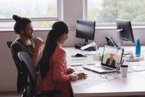 Uomo d'affari e donna di affari che ha una riunione di video conferenza in ufficio — Foto stock