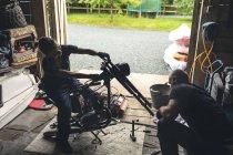 Mecanicistas masculinos e femininos reparando moto na garagem de reparação — Fotografia de Stock