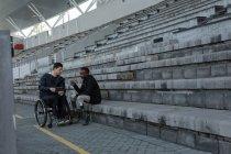Два спортсмена-инвалида обсуждают за цифровым планшетом в спортивном зале — стоковое фото