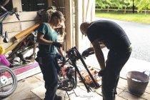Maschi e femminile meccanici riparazione moto nel garage di riparazione — Foto stock