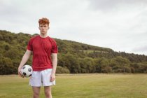 Young football player standing with soccer ball in the field — Stock Photo