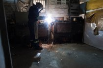 Side view of blacksmith using a welding torch in workshop — Stock Photo