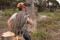 Rear view of lumberjack relaxing on tree stump in the forest — Stock Photo