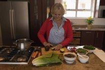 Senior woman cutting avocado in kitchen at home — Stock Photo