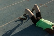Tired disabled athlete relaxing on a running track — Stock Photo