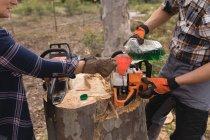 Deux bûcherons ravitaillant la scie à moteur en forêt à la campagne — Photo de stock