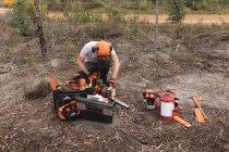 Bûcheron utilisant une tronçonneuse dans la forêt — Photo de stock