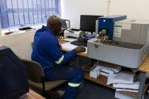 Vista lateral del herrero usando PC de escritorio en el taller - foto de stock