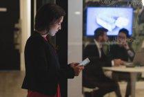 Femme d'affaires concentrée utilisant une tablette numérique au bureau — Photo de stock