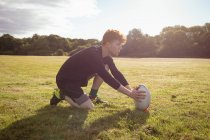 Rugby player placing rugby ball in the field on a sunny day — Stock Photo