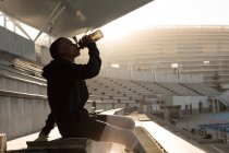 Side view of disabled athlete drinking water at sports venue — Stock Photo