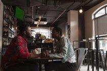 Vista laterale di coppia che interagisce tra loro nel caffè — Foto stock
