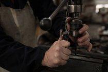 Крупный план кузнеца с помощью пресс-дрели в мастерской — стоковое фото