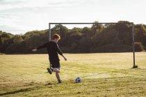 Jugador de fútbol pateando el fútbol en el campo en un día soleado - foto de stock