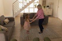 Großmutter und Enkelin tanzen im Wohnzimmer zu Hause — Stockfoto