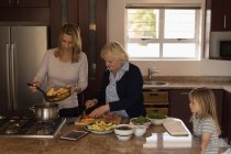 Multi-generation family cooking food in kitchen at home — Stock Photo
