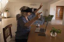 Vista lateral de la mujer mayor usando auriculares de realidad virtual en casa - foto de stock