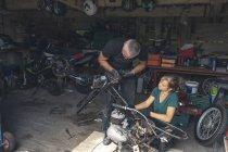 Mécaniciens masculins et féminins réparer moto dans le garage de réparation — Photo de stock