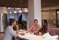 Деловые люди обсуждают чертежи в офисе — стоковое фото