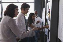 Unternehmensleiter diskutieren über Haftnotizen im Büro — Stockfoto
