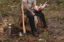 Lumberjack relaxing on tree stump in the forest — Stock Photo