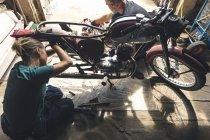 High angle view of mechanic repairing motorbike in garage — Stock Photo