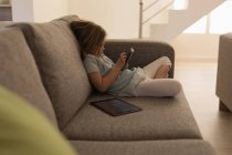 Girl using mobile phone in living room at home — Stock Photo