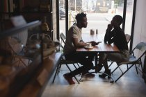 Side view of couple looking at each other in cafe — Stock Photo