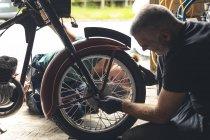 Mechanic repairing motorbike in repair garage — Stock Photo