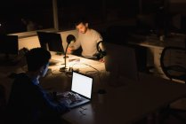 Two businessmen working on laptop in office during nighttime — Stock Photo
