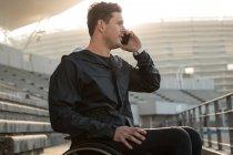 Atleta com deficiência conversando no celular em local de esportes — Fotografia de Stock