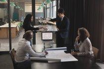 Dirigenti che discute sopra casa modello in sala conferenze presso ufficio — Foto stock