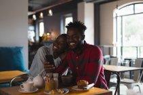 Heureux couple prendre selfie dans café — Photo de stock