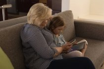 Grandmother and granddaughter using mobile phone and digital tablet in living room at home — Stock Photo