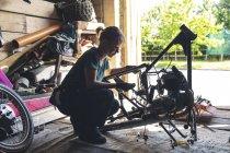Жіночий механік ремонту мотоцикл в гаражі — стокове фото