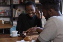 Glückliches Paar diskutiert über Handy im Café — Stockfoto