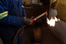 Mid section of blacksmith using a welding torch in workshop — Stock Photo