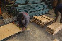 Arbeiter messen Holzplanken in der Seilerei — Stockfoto