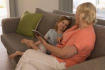 Grandmother and granddaughter using digital tablet in living room at home — Stock Photo
